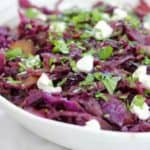 braised red cabbage topped with goat cheese and parsley in a white bowl