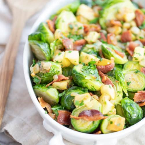 brussels sprouts withbacon and apples in a white dish