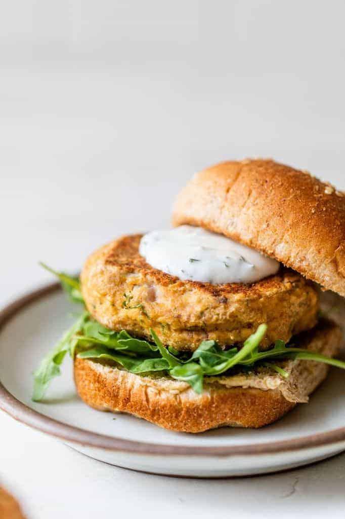 salmon burgers on a bun with arugula and dill sauce