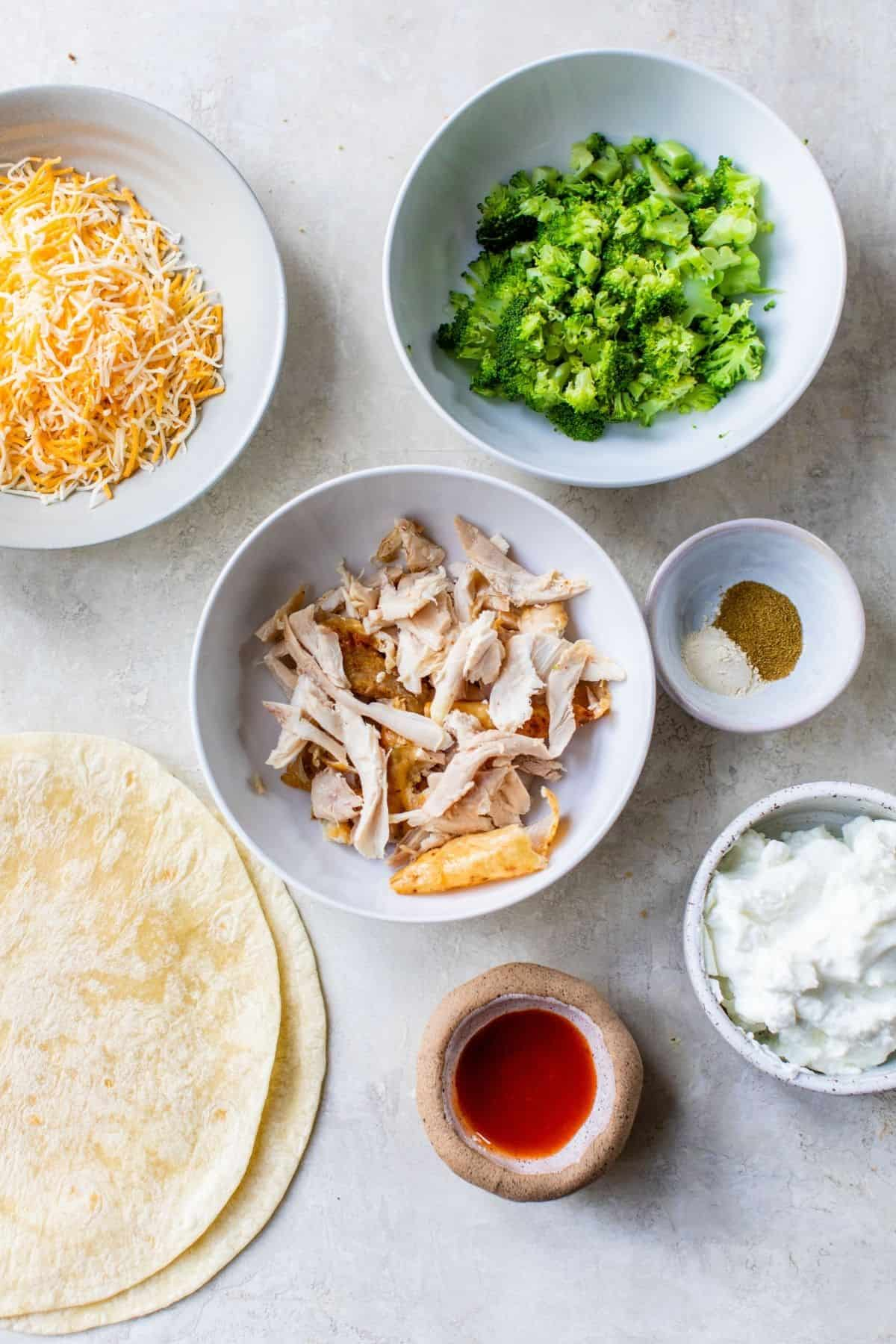 ingredients for chicken and broccoli quesadillas divided into small bowls
