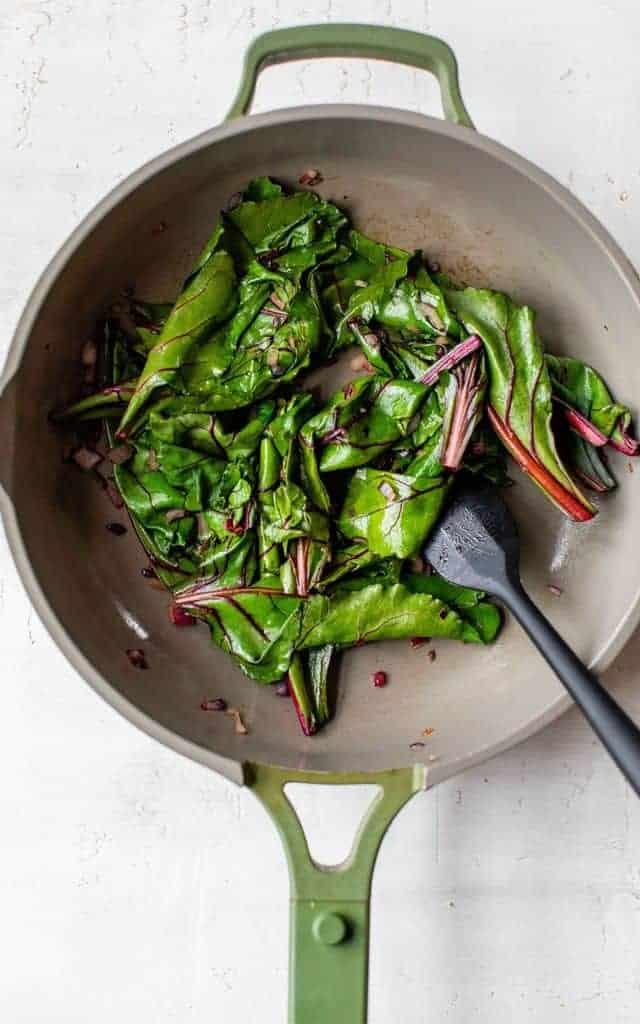 sautéing beet greens in a large skillet