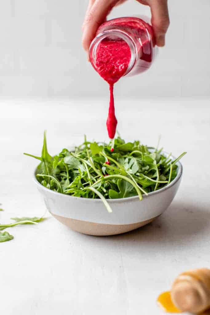 pouring beet salad dressing over a bowl filled with greens