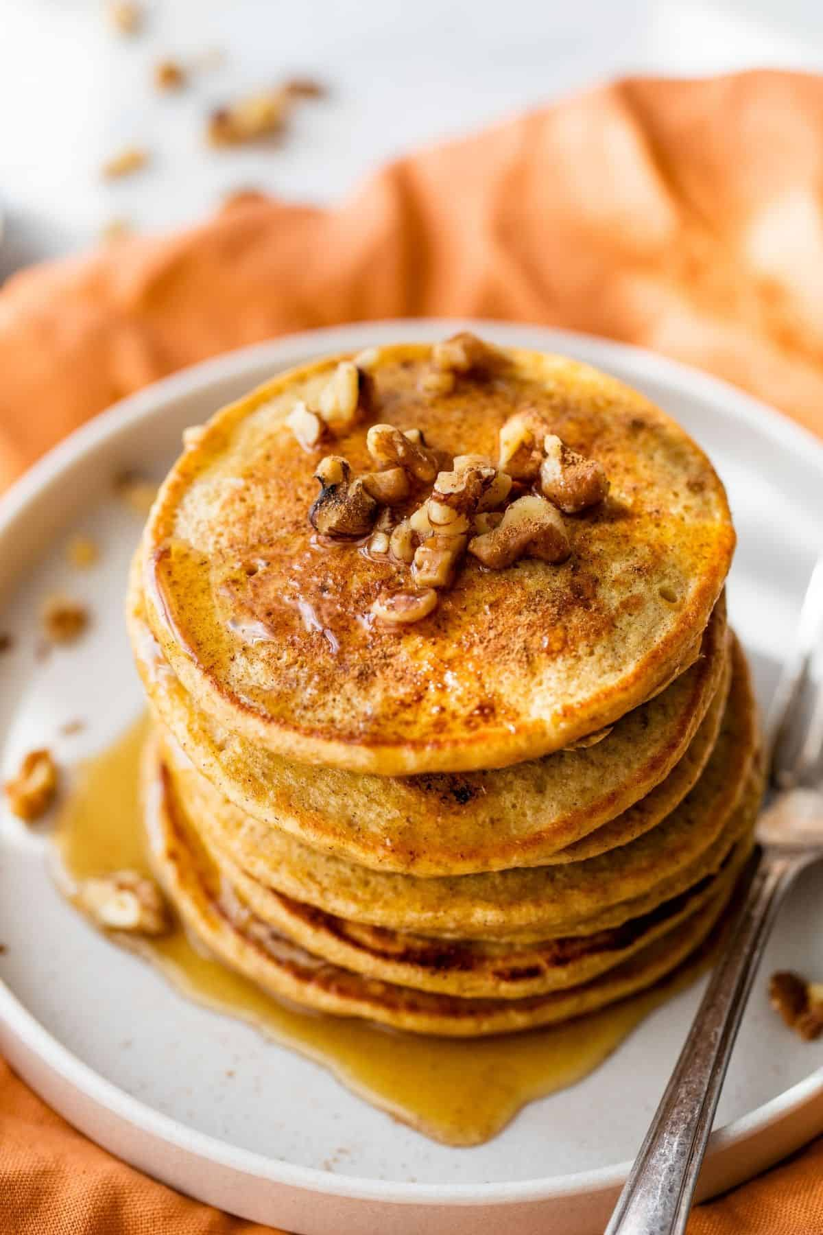 a stack of pumpkin protein pancakes served with chopped walnuts and maple syrup