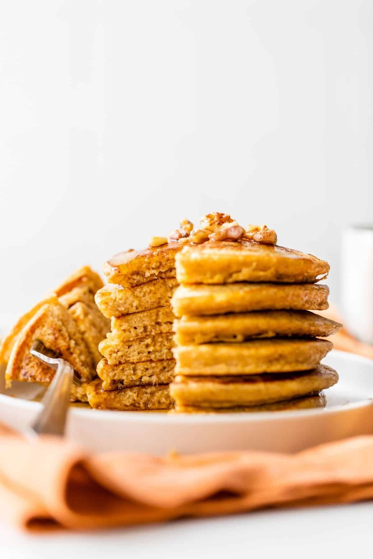 stack of pumpkin protein pancakes with maple syrup and chopped nuts