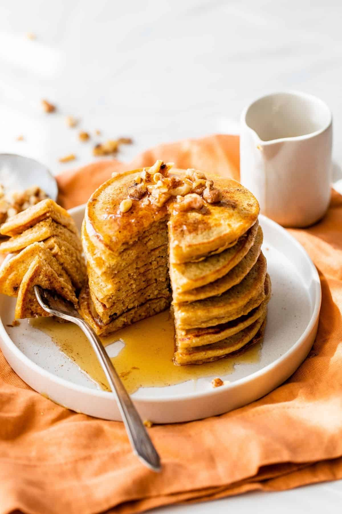 pumpkin pancakes with maple syrup and chopped nuts