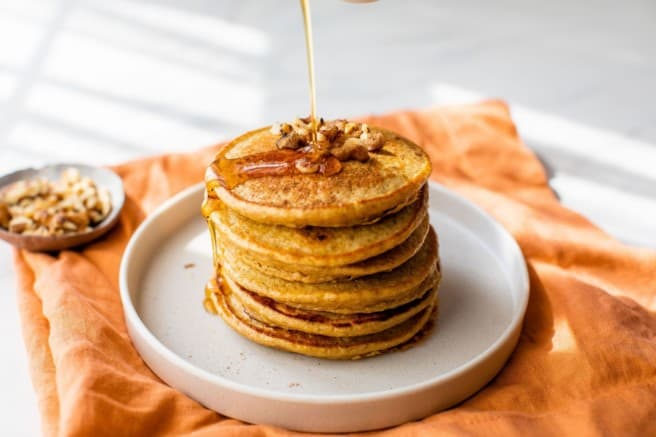 drizzle maple syrup over a stack of pancakes