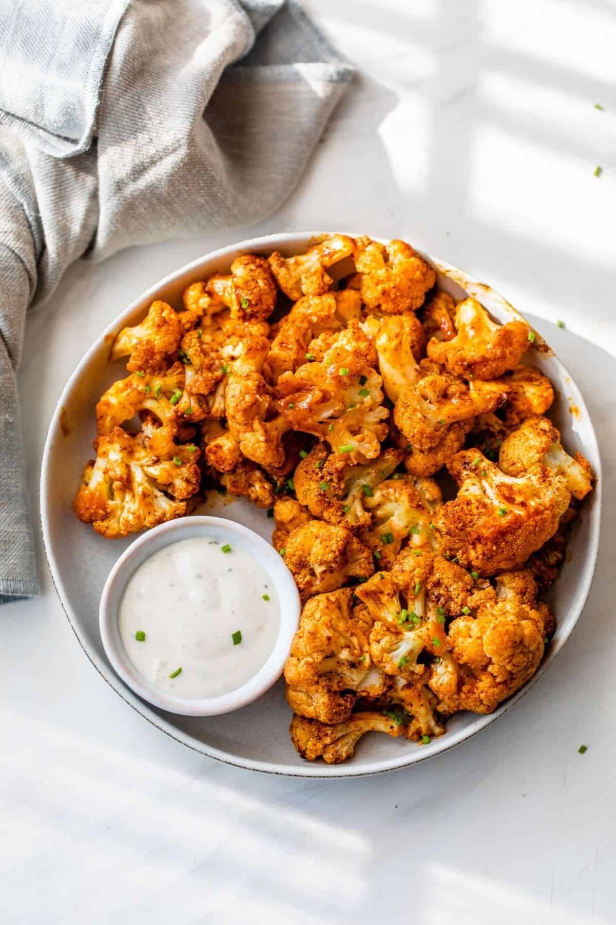 buffalo cauliflower bites served with blue cheese dressing on a serving plate