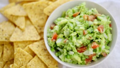 fresh guacamole in a white bowl served with corn chips