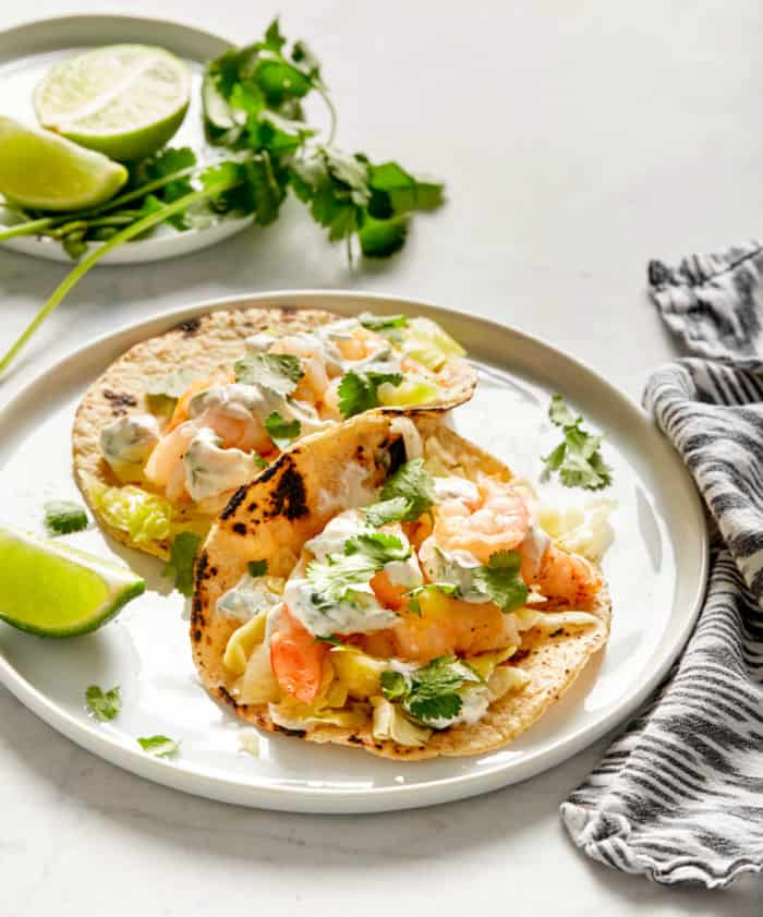 shrimp tacos in corn tortillas with a creamy sauce