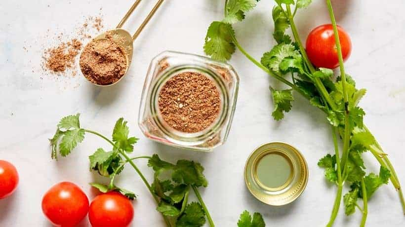 taco seasoning in a glass jar near tomatoes and cilantro