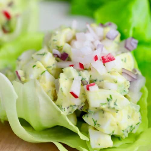 classic egg salad in a lettuce cup topped with diced radish and celery