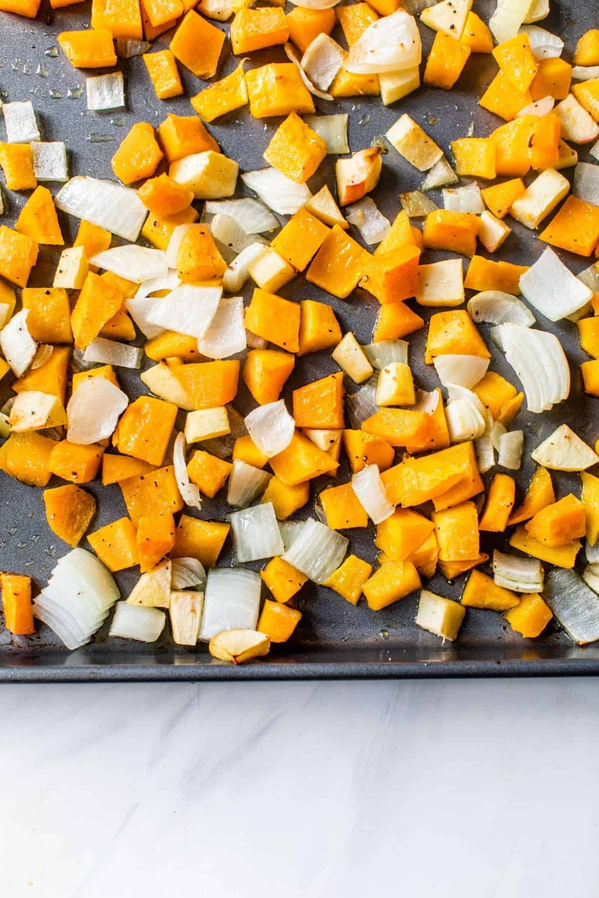 roasting butternut squash, onion and apple on a baking sheet