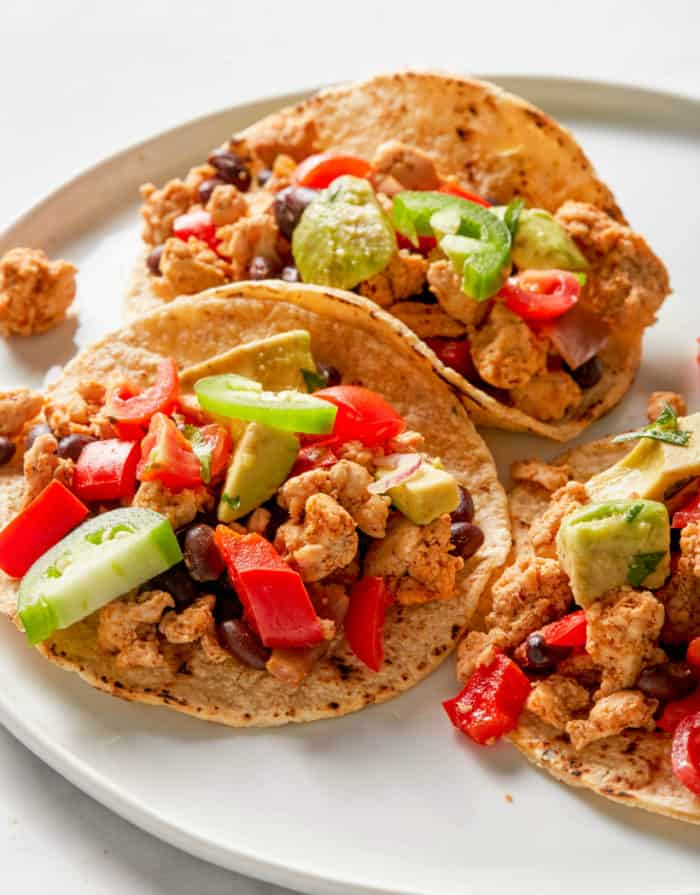 tacos made with ground turkey and black beans on a white plate