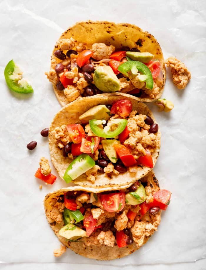three turkey tacos with toppings on parchment paper