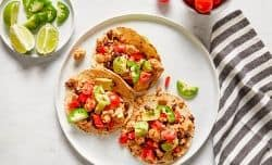 turkey tacos served in corn tortillas and topped with diced tomato, avocado and jalapeños