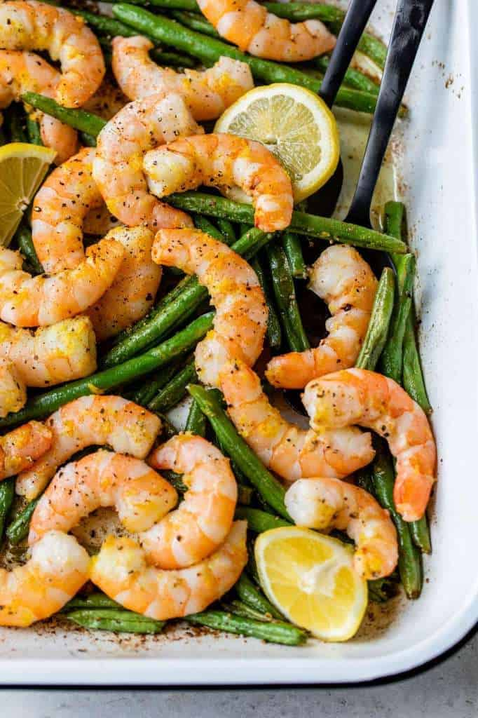 roasted shrimp and green beans in a white cooking dish