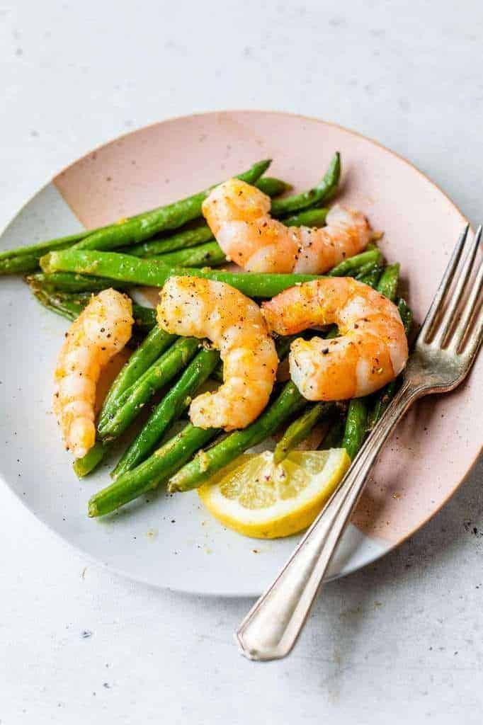 roasted shrimp and green beans served on a small plate