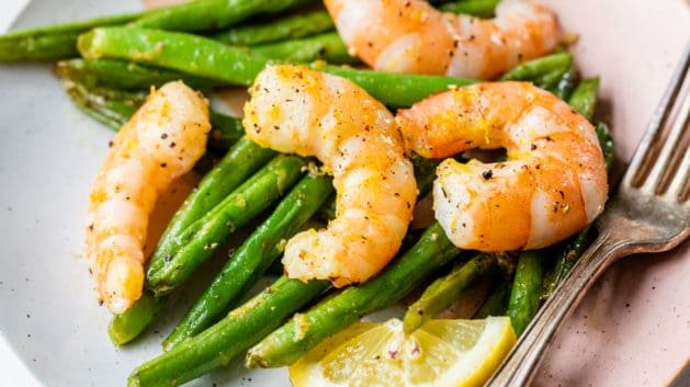 shrimp and green beans on small plate with fork