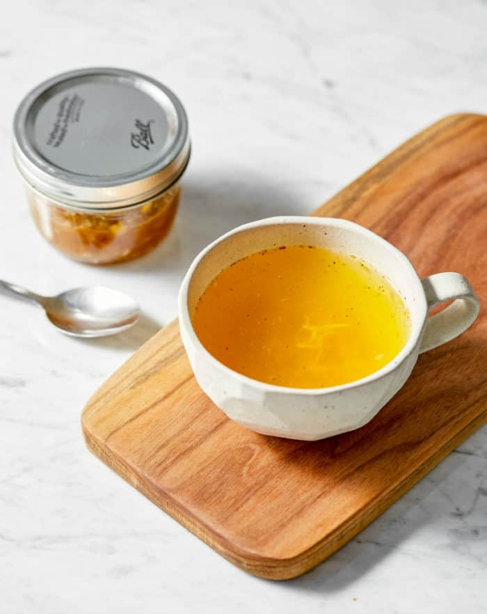 ginger turmeric tea in a mug on a wooden board