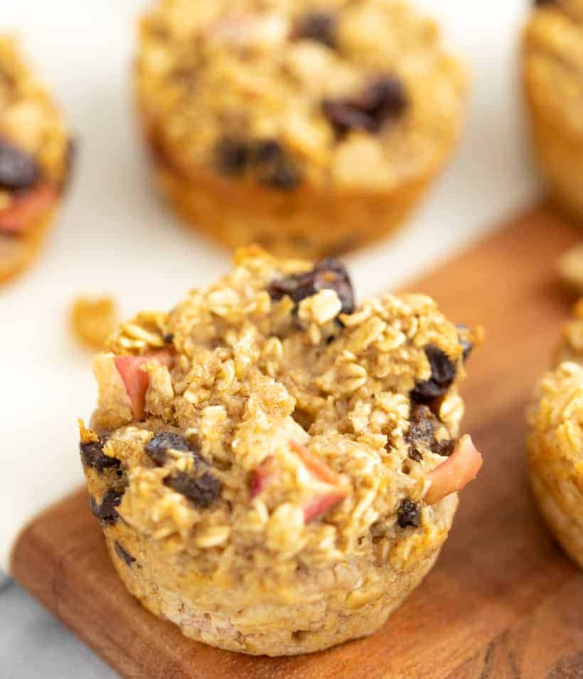 apple oatmeal muffins topped with apple oats and raisins