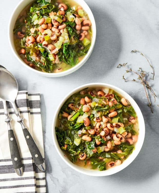 two bowls of black eyed peas with bacon and collard greens