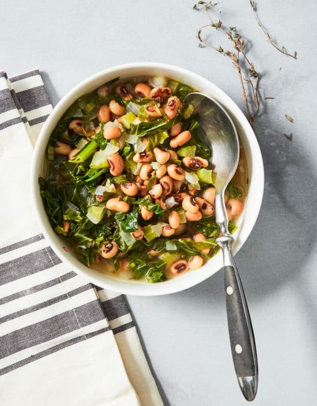 black eyed peas and collard greens served in a white bowl with a spoon