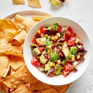 black bean salad mixed in a white bowl and served with tortilla chips