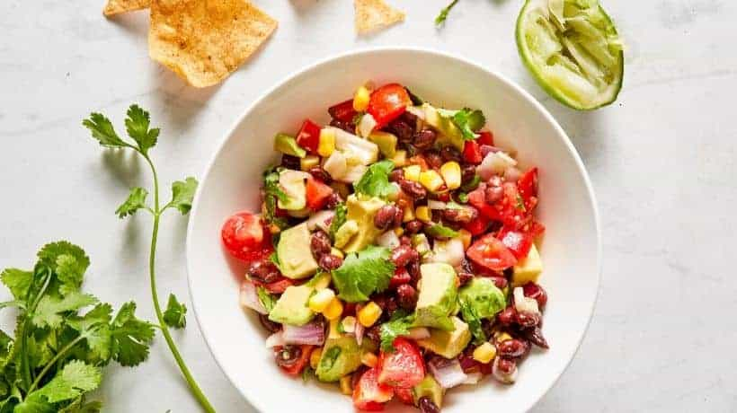 black bean salad with corn, tomatoes and avocado served with chips