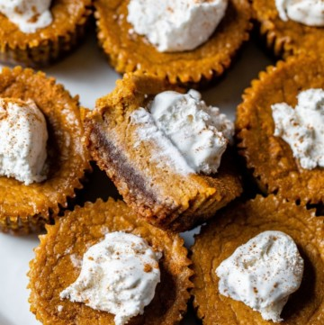 tray filled with mini pumpkin pies topped with whipped cream
