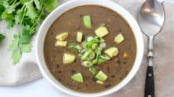 black bean soup in white bowl topped with scallions and avocados