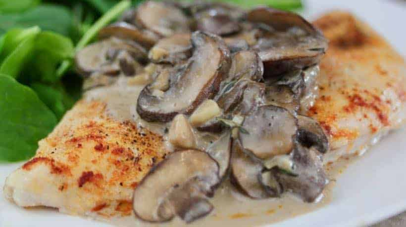 baked chicken breast topped with creamy garlic mushrooms and served with bright green arugula