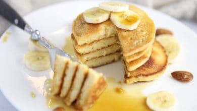 stack of fluffy almond flour pancakes topped with bananas and maple syrup on a white plate