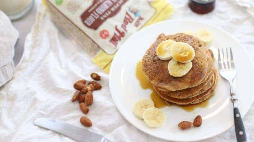 almond flour pancakes stacked on a white plate topped with bananas and maple syrup.