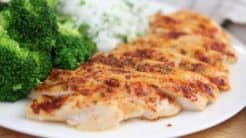 baked chicken breast on a white plate with jasmine rice and steamed broccoli