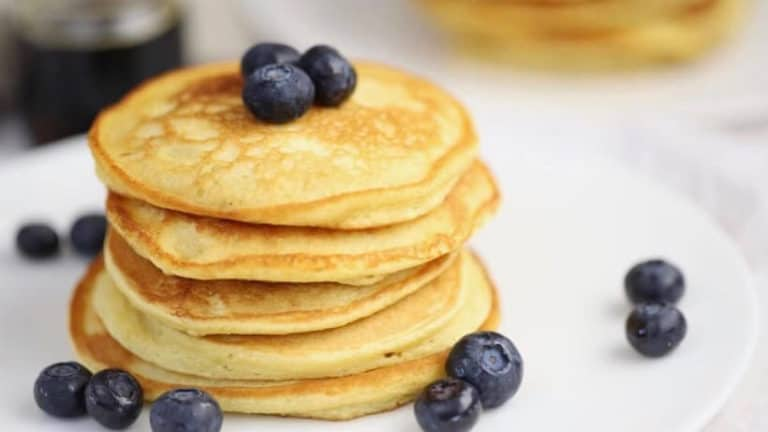 fluffy coconut flour pancakes on a white plate topped with juicy blueberries