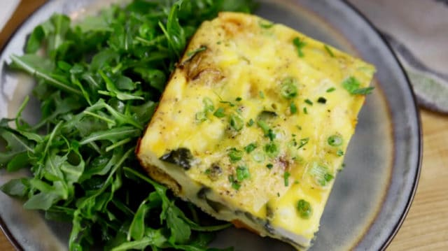 vegatable frittata on a plate served with arugula salad