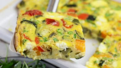 cut vegetable frittata being removed from pan with spatula