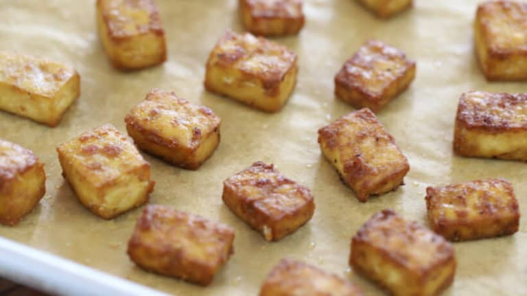 crispy baked tofu cubes on a rimmed baking sheet