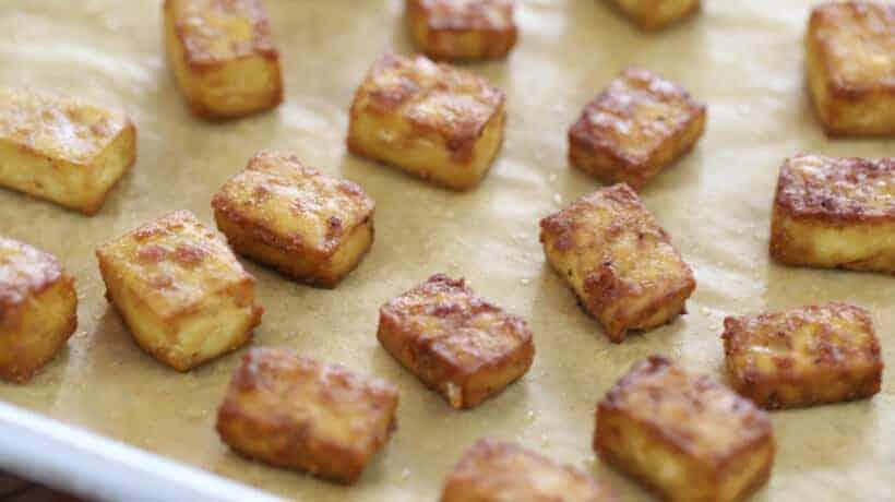 crispy baked tofu cubes on a rimmed baking sheet