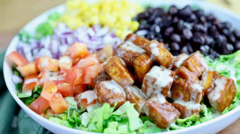 chopped salad topped with bbq tofu, corn, black beans tomatoes and red onion