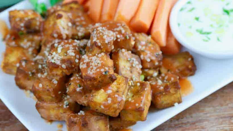 crispy baked buffalo tofu bites on a white plate with carrots and celery