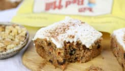 a bite out of gluten free carrot cake with yogurt cream cheese frosting