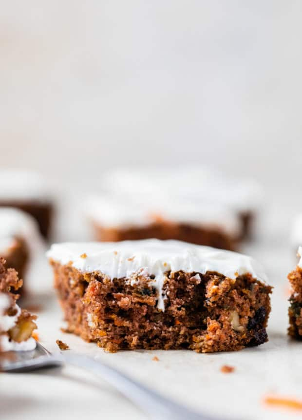 slice of gluten free carrot cake topped with cream cheese icing