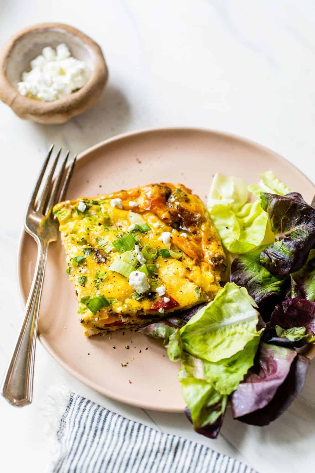 serving of healthy vegetable frittata on a plate with a salad
