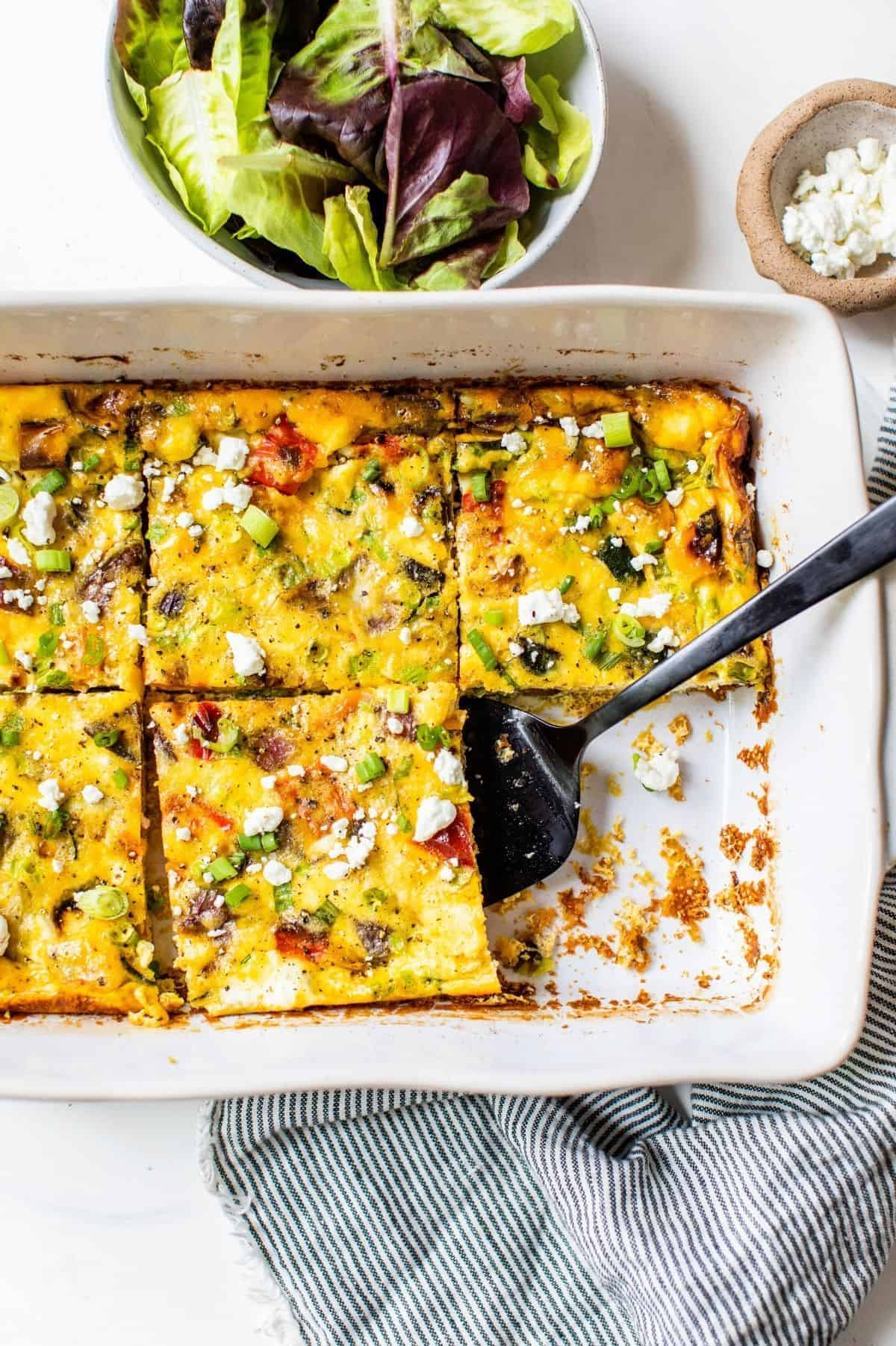 slicing a vegetable frittata in a baking dish