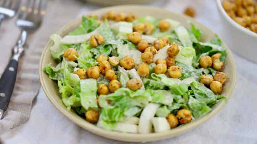 caesar salad topped with roasted chickpeas on a linen napkin