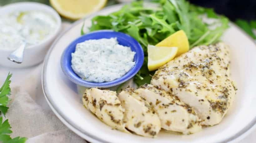 lemon garlic chicken on white plate with arugula salad, fresh lemon and dill sauce