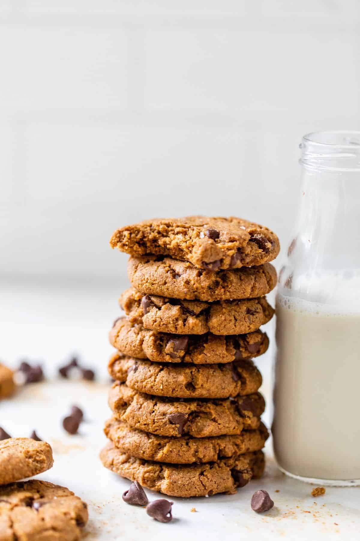 gluten-free chocolate chip cookies stacked against a glass of milk
