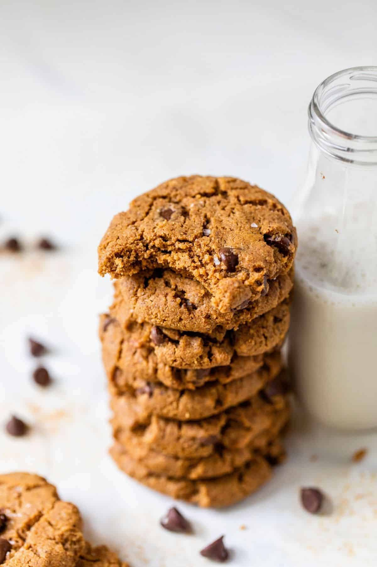 gluten-free chocolate chip cookies stacked near a jar of milk