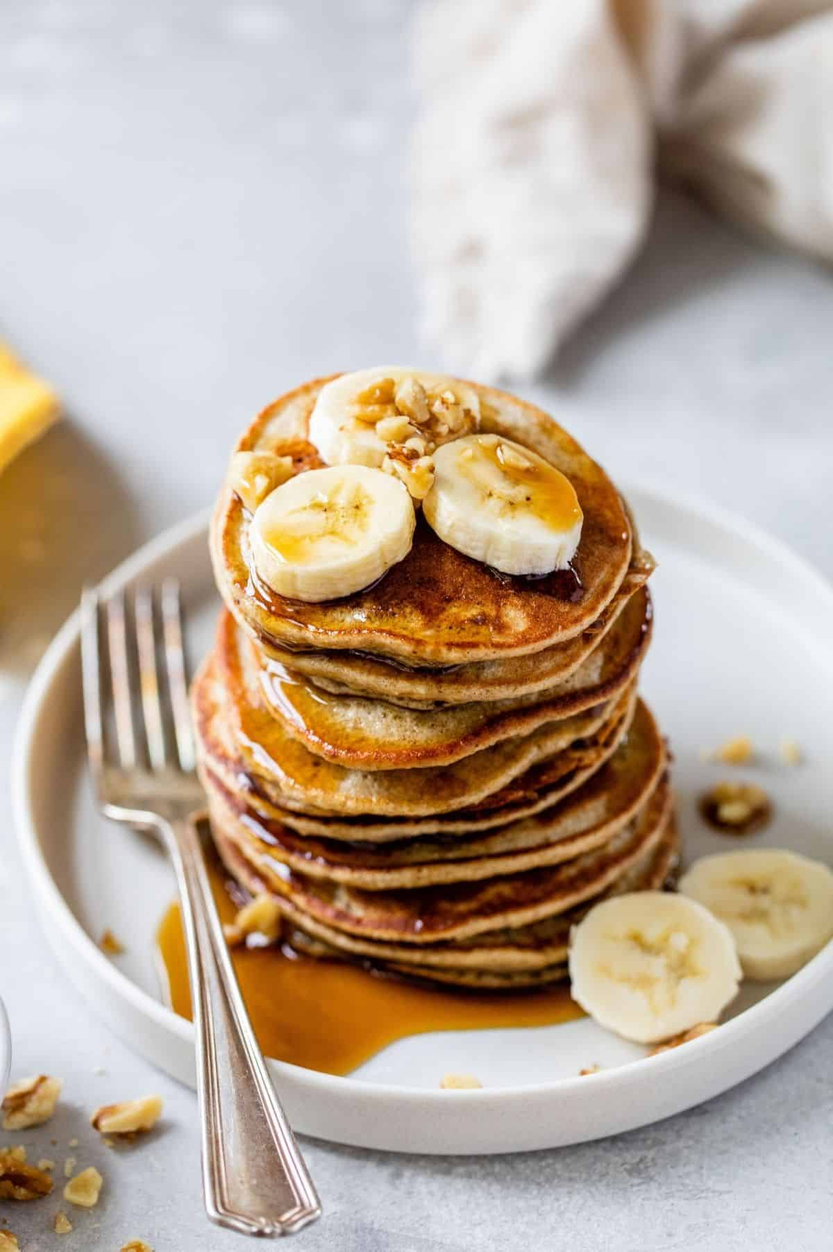 a stack of banana oatmeal pancakes topped with banana slices, chopped nuts and maple syrup